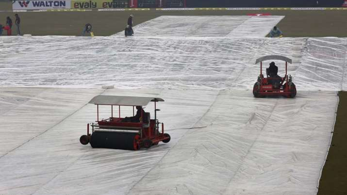 Ground staff work to dry the pitch and field following a