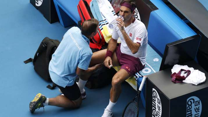 India Tv - Switzerland's Roger Federer receives treatment from a trainer during his quarterfinal against Tennys Sandgren of the U.S. at the Australian Open tennis championship in Melbourne