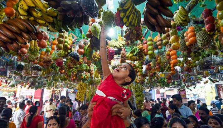 India Tv - Chennai: A young girl attempts to touch decorations hanging from a roof on the first day of the New