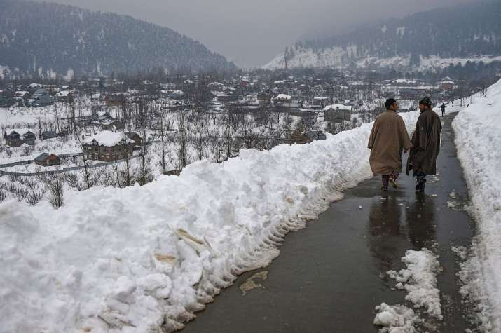 Srinagar: Men walk on a road along a snow-covered village