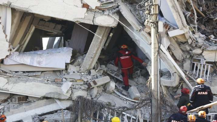 India Tv - Rescuers work on searching for people buried under the rubble on a collapsed building, after an earthquake struck Elazig, eastern Turkey