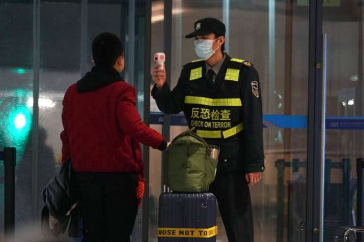 An airport staff member uses a temperature gun to check