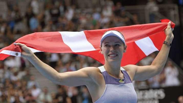 Denmark's Caroline Wozniacki unfurls Denmark's flag after