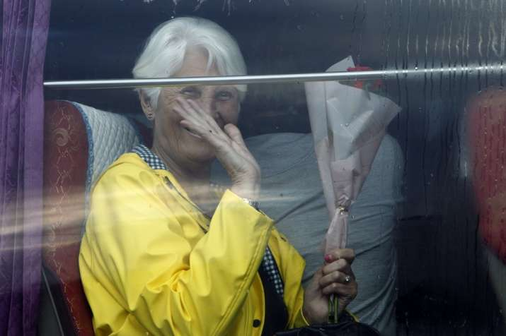 India Tv - A passenger waves from a bus after she disembarked from the MS Westerdam, owned by Holland America L