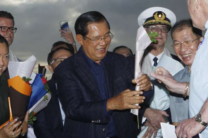 India Tv - Cambodia's Prime Minister Hun Sen, center, gives a flower to a passenger who disembarked from the MS