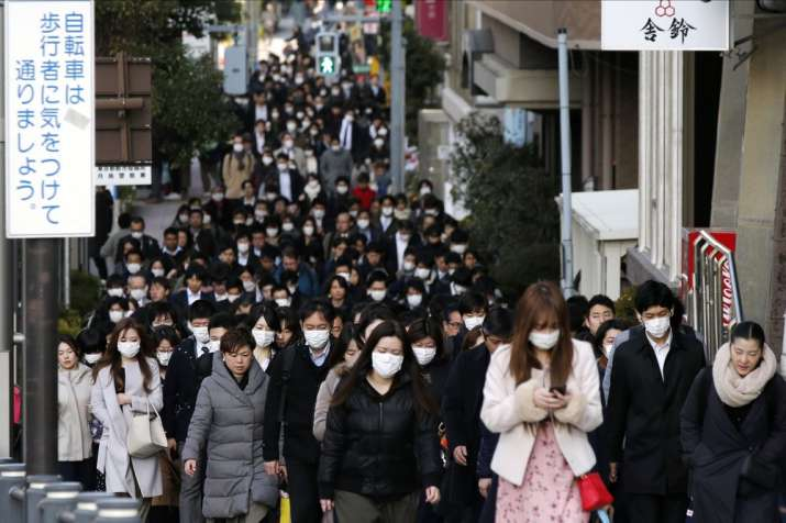 In this Feb. 20, 2020, file photo, people wear masks as they commute during the morning rush hour in