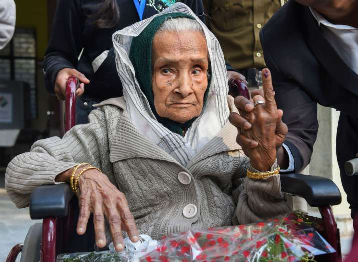 India Tv - 111-year-old Kalitara Mandal shows her finger marked with indelible ink after casting vote during the Delhi Assembly elections at Chittaranjan Park polling station