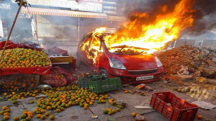 India Tv - A car in flames near a vandalised fruit shop during clashes between a group of anti-CAA protestors and supporters of the new citizenship act, at Chand Bagh in north-east Delhi