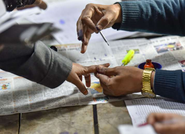 India Tv - A polling official applies indelible ink on the finger of a voter during the Delhi Assembly elections at a polling station, in Jafrabad area of Delhi