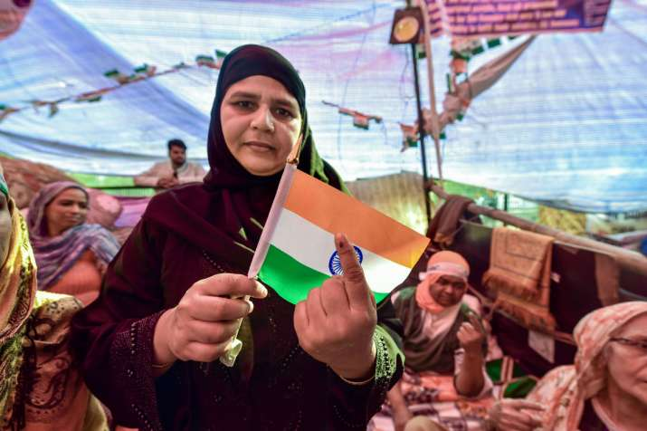 India Tv - A protestor, holding a tricolour, shows her ink-marked finger after casting vote for the Delhi Assembly elections, at the site of their peaceful agitation against the Citizenship Act, in Shaheen Bagh