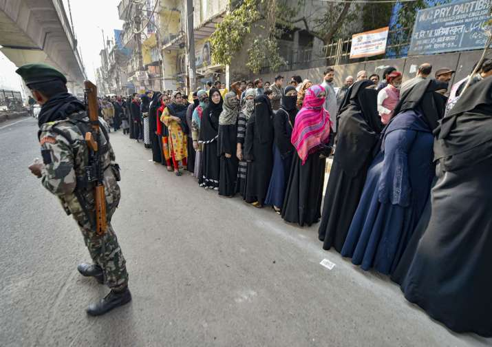 India Tv - A security personnel stands guard as voters stand in a queue to cast vote during the Delhi Assembly elections at a polling station, in Jafrabad area