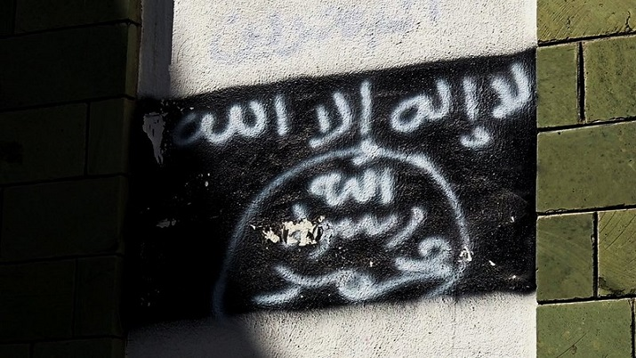 The black al-Qaida flag is sprayed on the wall of a damaged school that was turned into a religious