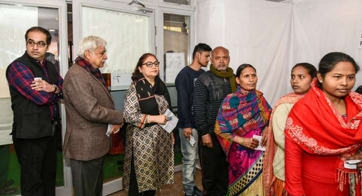 India Tv - Chief Election Commissioner Sunil Arora (2L), his wife Ritu Arora (3L) along with others stand in a queue to cast their vote for Delhi Assembly polls, at Nirman Bhawan polling station