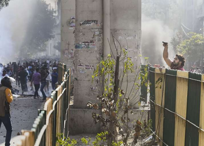 A protestor (R) brandishes a pistol during clashes between