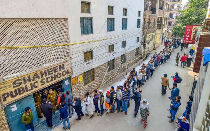 India Tv - People wait to cast their votes at Shaheen Public School polling station in the Shaheen Bagh area, which has been witnessing a peaceful protest against the Citizenship Act for several weeks