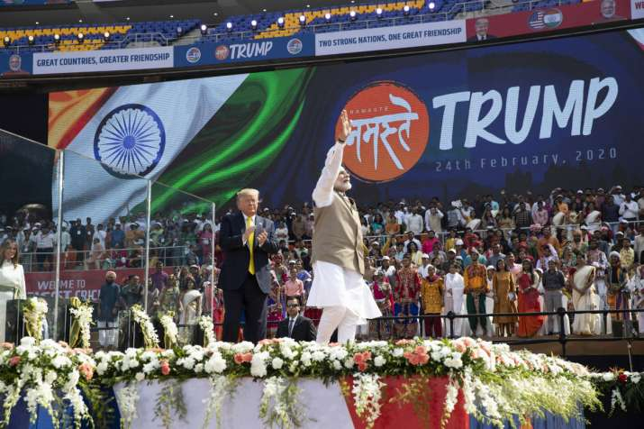 India Tv - US President Donald Trump applauds and Indian Prime Minister Narendra Modi waves after a Namaste Trump event at Sardar Patel Gujarat Stadium