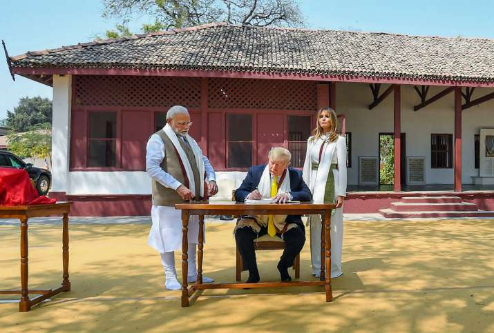 India Tv - US President Donald Trump signs the visitor's book as Prime Minister Narendra Modi and First Lady Melania Trump looks on at Sabarmati Ashram in Ahmedabad Monday Feb