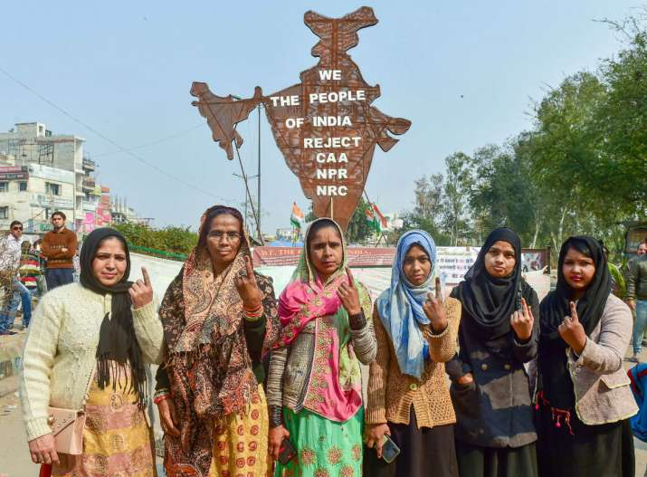 India Tv - Protestor show their ink-marked fingers after casting votes for the Delhi Assembly elections, near the site of their peaceful agitation against the Citizenship Act, in Shaheen Bagh