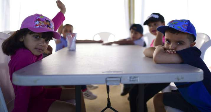 Kindergarten students from a school sit at a plastic table