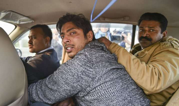 Police take away an unidentified person after he allegedly opened fire in the Shaheen Bagh area of N