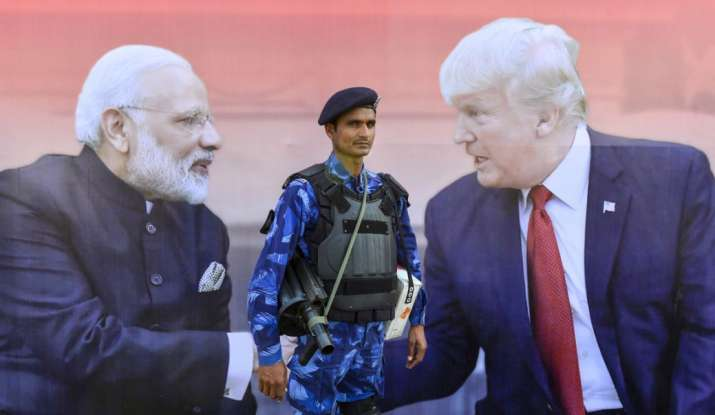 India Tv - A security man stands guard near a bill board showing pictures of Prime Minister Narendra Modi and U