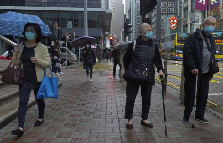 India Tv - People wearing protective face masks walk on a street in the rain in Hong Kong, Friday, Feb. 14, 2020. COVID-19 viral illness has sickened tens of thousands of people in China since December.