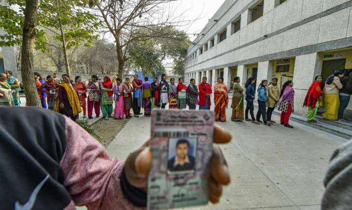 Voters stand in a queue to cast votes during the Delhi