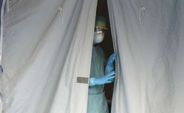A medical staffer watches from a tent at one of the emergency structures that were set up to ease pr