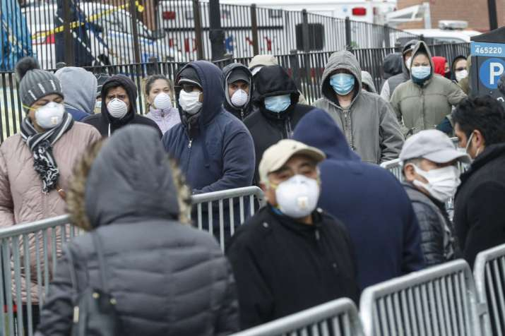 Patients wear personal protective equipment while maintaining social distancing as they wait in line