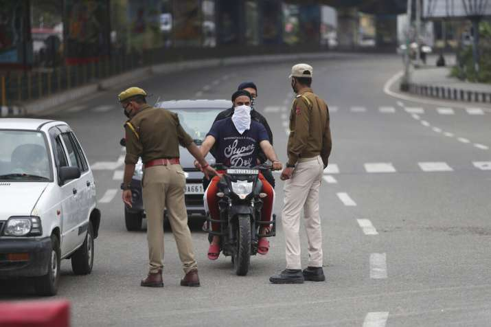 Policemen question commuters during lockdown in Jammu, India, Wednesday, March 25, 2020. The world's