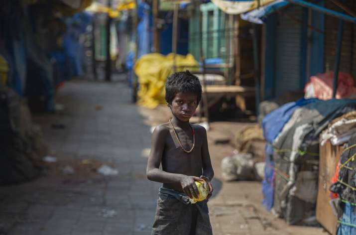 A homeless boy collects rotten fruits from a deserted fruit market during lockdown in Gauhati, India