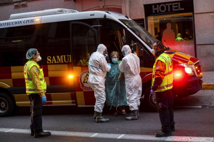 A patient, center, is transferred to a medicalised hotel during the COVID-19 outbreak in Madrid, Spa