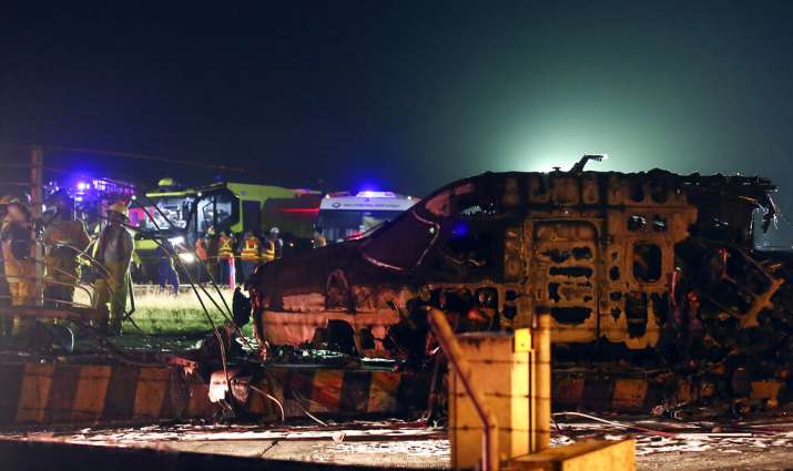 Firemen and rescuers talk beside the remains of a Lion Air, West Wind 24 aircraft after it caught fi