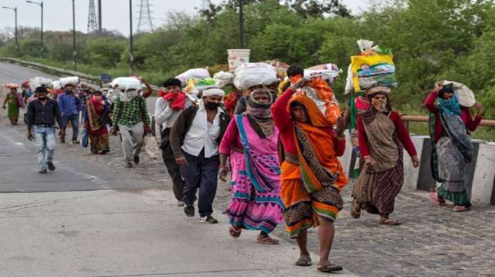 Migrant labourers along with their families walk on a