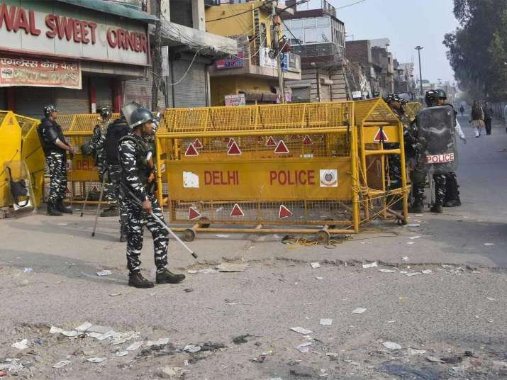 Police stand guard in a riot-affected locality of northeast