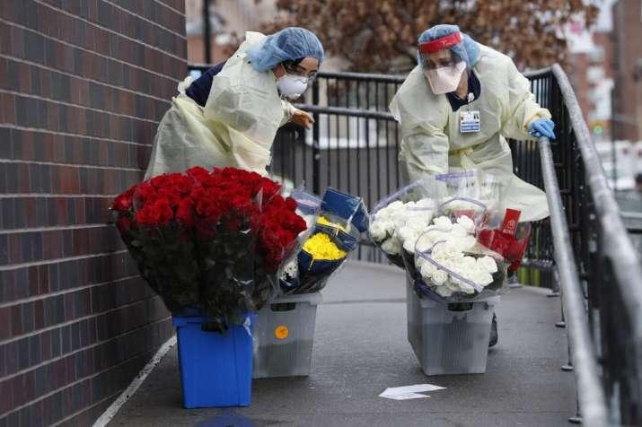 Emergency room nurses transport buckets of donated flowers up a ramp outside Elmhurst Hospital Cente