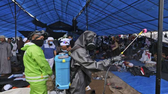 Paramilitary police officers in hazmat suit disinfect a tent built on a field where a mass congregat