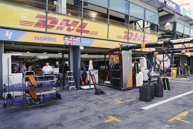 Technicians work around equipment and car parts in the The