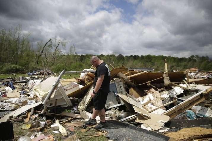 Aaron Pais kicks around debris at a mobile home park after a tornado hit on Monday, April 13, 2020,