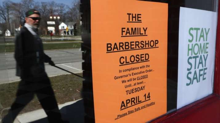 A pedestrian walks by The Family Barbershop, closed due to