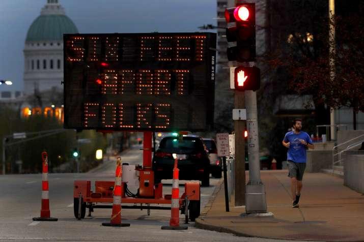 A person jogs past a sign encouraging social distancing Thursday, April 2, 2020, in St. Louis. The c