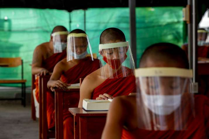 Novice Buddhist monks with protective masks and face shields, seated to maintain social distancing p
