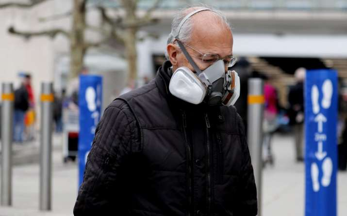 A shopper wears a face mask as he queues at a supermarket due to the coronavirus related lockdown in