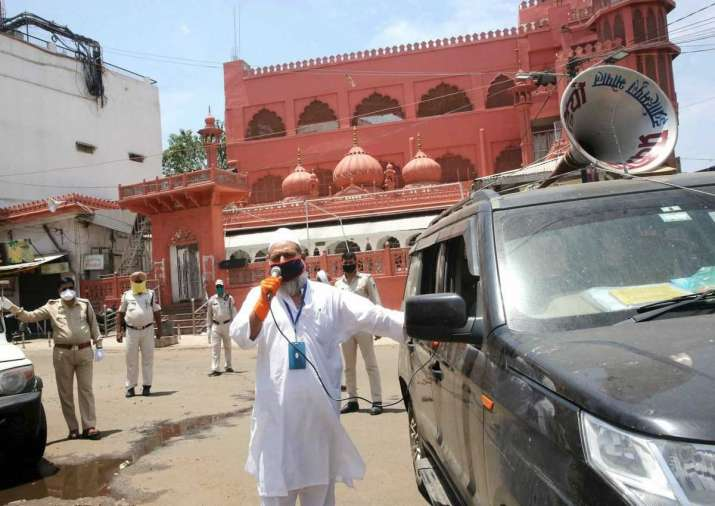A Muslim devotee makes announcements urging members of the
