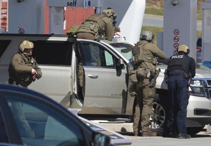 Royal Canadian Mounted Police officers surround a suspect at a gas station in Enfield, Nova Scotia,