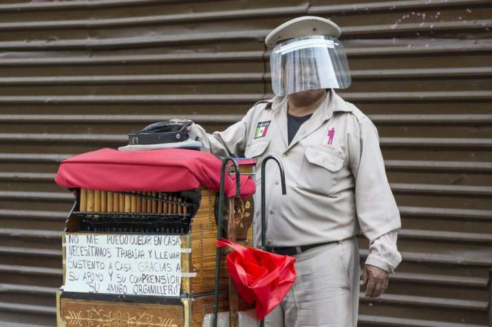 A barrel organ player wearing a face shield as a precaution against the spread of the new coronaviru