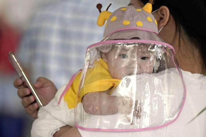 A baby with a face shield waits to board a plane at an airport in Wuhan, central China's Hubei Provi