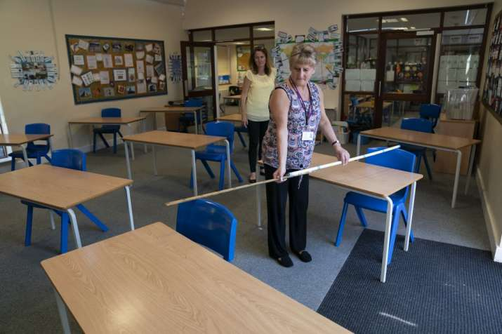 Year 6 teacher Jane Cooper uses a 2 meter length of ruler and pipe to check seat spacings in her cla