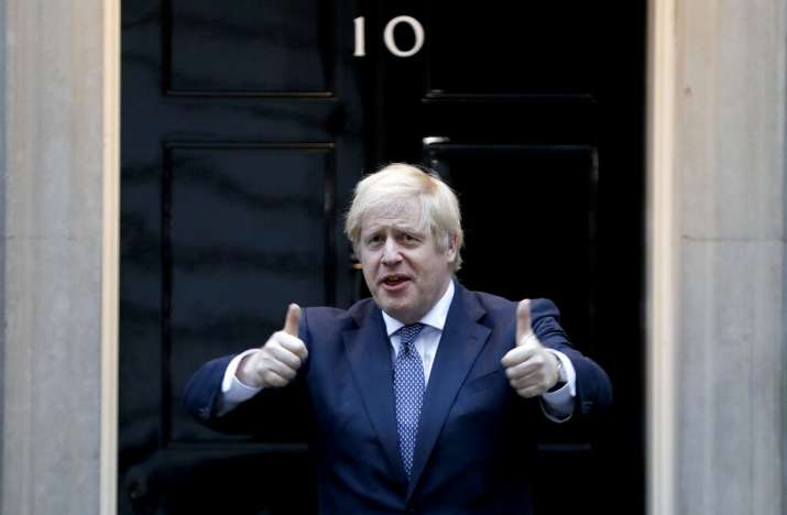 Britain's Prime Minister Boris Johnson shows thumbs up before he applauds on the doorstep of 10 Down