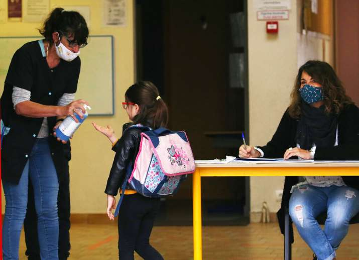 A school child uses an disinfectant solution as she arrives at her school in Saint Jean de Luz, sout